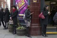 Women buried in the phone, waiting for the subway around Covent Royalty Free Stock Images