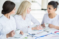 Women in business. Group of beautiful business women working on new business strategy at office and drinking coffee royalty free stock image