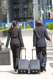 Women Business Travellers With Rolling Suitcases. Rear view of two young women business executives wearing suits walking through a city with rolling suitcases Stock Image