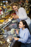 Women buying dark and white chocolate filled candies Royalty Free Stock Images
