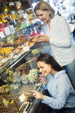 Women buying dark and white chocolate filled candies Stock Photos