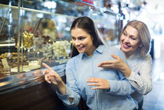 Women buying dark and white chocolate filled candies Royalty Free Stock Photo