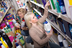 Women buying detergents. Two female customers choosing detergents for house in the shopping mall Stock Image