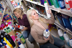 Women buying detergents. Two ordinary women choosing detergents for house in the shopping mall Stock Photo