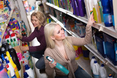 Women buying detergents. Two ordinary female customers choosing detergents for house in the shopping mall Stock Photo