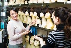 Women buying modern periwigs Stock Photos