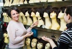 Women buying modern periwigs Royalty Free Stock Photo