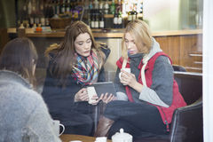 Women in a cafe with a digital tablet Stock Images