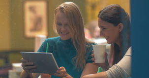 Women in Cafe Laughing at Something in Tablet PC. Two women are sitting in cafe and laughing at something they see in tablet PC. Shot is made through cafe show stock video footage