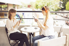 Women in cafe with mobile phone and tablet Stock Photos