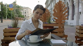 Women in cafe reading menu. Professional shot on BMCC RAW with high dynamic range. You can use it e.g in your commercial video, business, presentation stock video footage