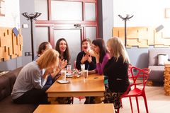 Women in cafe. Thirty years old girlfriends are sitting in cafe and talking royalty free stock image