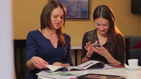 Women in cafe watching photos reading magazines fashion vogue. Stock footage stock footage