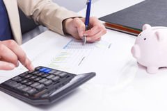 Women calculate expenses. With calculator and piggybank Stock Photos