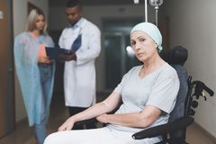 A woman with cancer, with a doomed look, is sitting in a wheelchair. Behind her daughter stands and talks to the doctor. A women with cancer, with a doomed look Stock Photo
