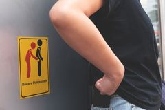 Women are careful pickpocket because she see beware pickpockets sign symbol. stock images