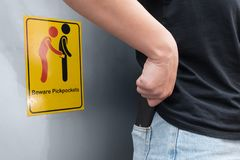 Women are careful pickpocket because she see beware pickpockets sign symbol. stock photography