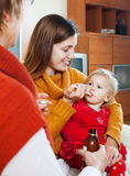 Women caring for sick toddler at home. Two women caring for sick toddler at home Royalty Free Stock Image