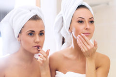 Women caring of their faces looking into mirror. reflection beautiful girls Royalty Free Stock Photos