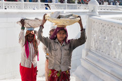 Women carry basket of stones on their head at Golden Temple. Amritsar. India Royalty Free Stock Photography