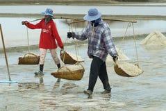 Women carry salt at the salt farm in Huahin, Thailand. Stock Photo