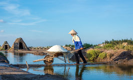 Women carry salt from salt farm to store royalty free stock photo