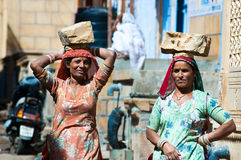 Women carrying bricks on a construction site in India. JAISALMER, INDIA - FEB 26: women carry a brick on their head on a construction site on Feb 26, 2013 in Stock Photography