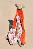 Women carrying bricks on a construction site in India. JAISALMER, INDIA - FEB 25: A woman carries a brick on her head on a construction site on Feb 25, 2013 in Stock Photo
