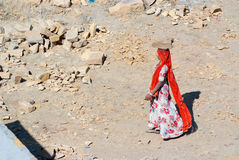Women carrying bricks on a construction site in India. JAISALMER, INDIA - FEB 25: A woman carries a brick on her head on a construction site on Feb 25, 2013 in Royalty Free Stock Image