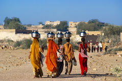 Women carrying water in Rajasthan. RAJASTHAN, INDIA – FEB 27: women lugging a water pot on their head on February 27, 2013 in Rajasthan, India. Due to the lack Royalty Free Stock Image