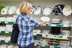 Women with cart shopping buys plate in supermarket Stock Photos