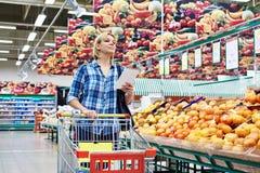 Women with cart shopping fruits Stock Photos