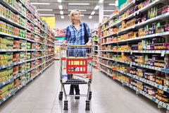 Women with cart shopping in supermarket. Women housewife with cart shopping in supermarket Royalty Free Stock Photo