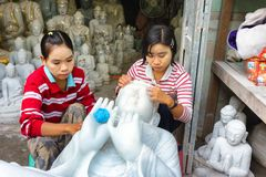 Women carving Buddha statue Royalty Free Stock Image
