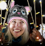Women with cat winter hat smiling next to the Outdoor Christmas decorations Royalty Free Stock Image