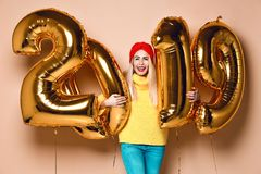 Women celebrating New Year xmas party happy laughing in yellow sweater blouse with 2019 gold balloons stock image