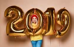 Women celebrating New Year xmas party happy laughing in yellow sweater blouse with 2019 gold balloons stock photo