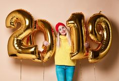 Women celebrating New Year xmas party happy laughing in yellow sweater blouse with 2019 gold balloons royalty free stock photo