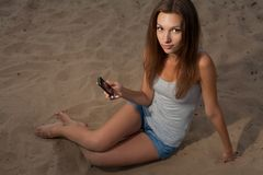 Women with cell phone sitting on sand Royalty Free Stock Photography