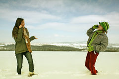 Women on cellphones in winter. A view of two women standing in a field covered with snow, talking on cellphones Royalty Free Stock Photo