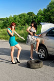 Women changing a tire Stock Image