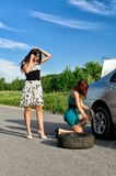 Women changing a tire Royalty Free Stock Photography