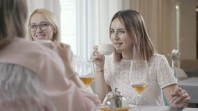 Women chatting in a cafe and drinking tea: breakfast with a friend. Two young women - sisters or friends - are similar to each other: sit in a cafe and stock video