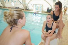 Women chatting by side pool Stock Image