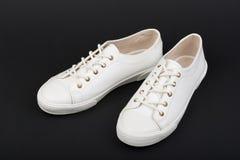 Women& x27 ; chaussures blanches de sport de s sur le fond foncé Photo libre de droits