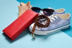 Women& x27 ; chaussures de s et accessoires de voyage sur un fond en pastel bleu Sac, bourse, espadrilles, coquille, ceinture Images stock