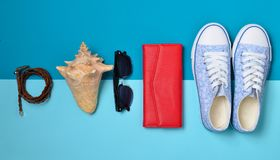 Women& x27 ; chaussures de s et accessoires de voyage sur un fond en pastel bleu Sac, bourse, espadrilles, coquille, ceinture Con Photos libres de droits