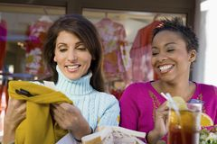 Women Checking Clothes At Cafe Stock Image
