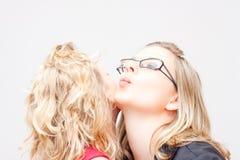 Women cheek kiss Stock Image