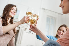 Women cheering with wine. Three young attractive women cheering with white wine and smiling stock image